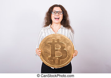 Happy young business woman holding a Golden Bitcoin. Virtual money.
