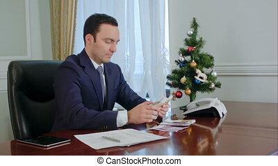 Happy young businessman counts salary near New Year tree in office