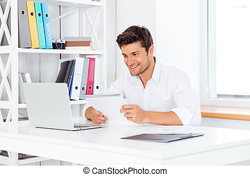 Happy young businessman holding notepad and looking at computer screen