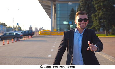 Happy young businessman in a formal black suit funny dancing and singing while going with luggage on city street after flight. Cheerful handsome man celebrating his achievement and success. Close up