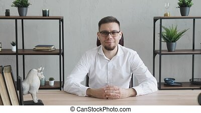 Happy young businessman in office in glasses sitting at table looking at camera.