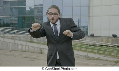 Happy young businessman in suit and tie wearing glasses funny dancing joyfully in nature in front of the corporation