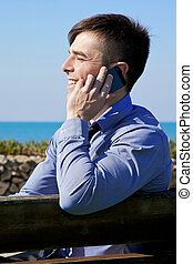 Happy young businessman on the phone smiling in front of the ocean
