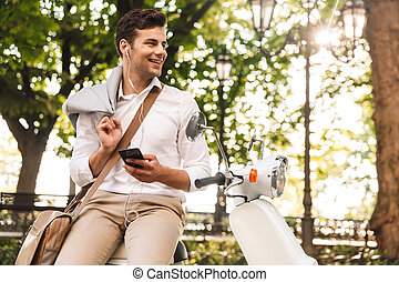 Happy young businessman sitting on a motorbike outdoors