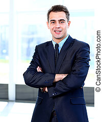 Happy young businessman smiling at office
