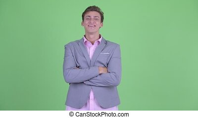 Happy young businessman smiling with arms crossed - Studio...