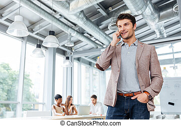 Happy young businessman talking on cell phone in office