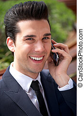 Happy young businessman talking on the phone outdoors