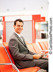 happy young businessman using tablet at airport