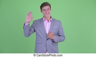 Happy young businessman waving hand