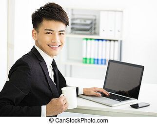 happy young  businessman with laptop in office