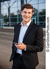 Happy young businessman with mobile phone standing outdoors