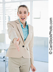 Happy young businesswoman reaching her hand friendly