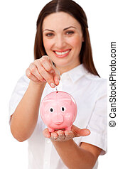 Happy young businesswoman saving money in a piggybank