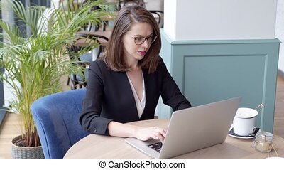 Happy young businesswoman using laptop computer in a cafe
