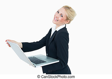 Happy young businesswoman using laptop