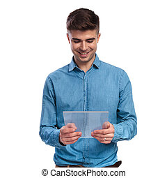 happy young casual man holding a transparent futuristic tablet