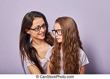 Happy young casual mother speaking and looking on her angry serious kid in fashion glasses and hugging on purple background with empty copy space