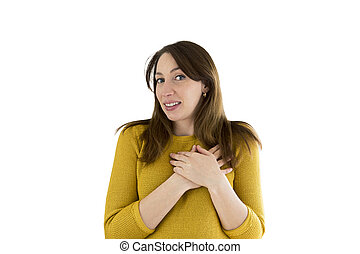 Happy young casual woman holding her hands by her heart with natural emotional enjoying face. Love concept