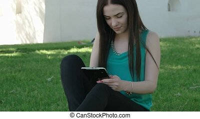 Happy young Caucasian brunette woman with tablet in park on sunny summer day sitting on grass, smiling, looking at tablet screen. Modern lifestyle and relaxation concepts.