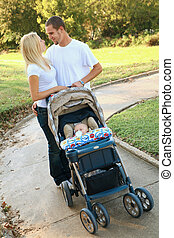 Happy Young Caucasian Couple Walking Their Baby