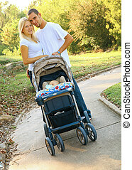 Happy Young Caucasian Couple With Baby In Park