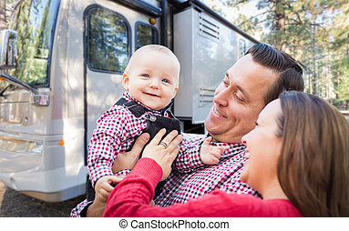 Happy Young Caucasian Family In Front of Their Beautiful RV At The Campground.