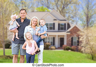 Happy Young Caucasian Family Outside  In Front of Their New Home
