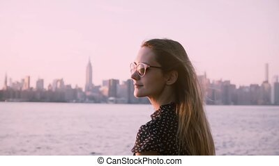 Happy young Caucasian girl in sunglasses with hair blowing in the wind watching sunset at city river beach slow motion.