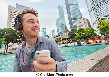Happy young Caucasian man listening to music on smartphone holding mobile phone wearing headphones in city outdoors downtown of Hong Kong, China. Asia travel tourist.