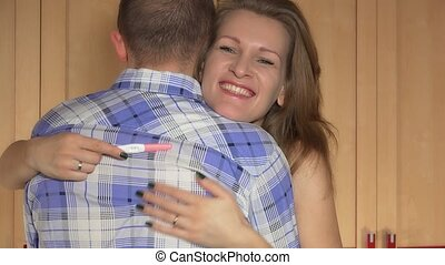 happy young caucasian woman embracing man after positive pregnancy test