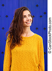 Happy young caucasian woman looking away and smiling against blue background