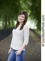 Happy young Caucasian woman standing in park. - Pretty young...