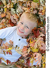 Happy Young Child Jumping in Pile of Fall Leaves