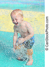 Happy Young Child Playing in Toddler Splash Pool