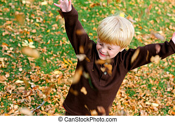 Happy Young Child Playing Outside in The Fallen Leaves