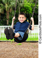 Happy young child swinging