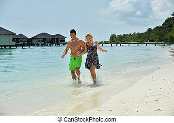 happy young  couple at summer vacation have fun and relax at beautiful sunny  day on beach