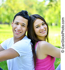 Happy young couple back to back in park