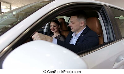 Happy young couple buying a car in a modern auto show. Close-up.