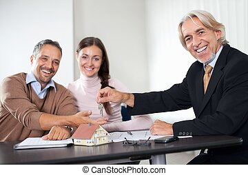 Happy young couple buying new home with agent