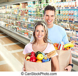 shopping - Happy young couple carrying shopping bags with...