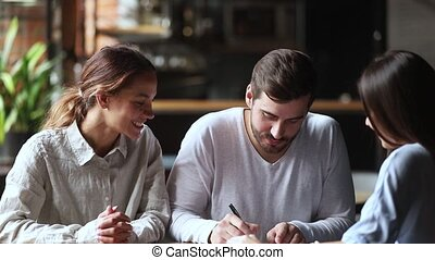 Happy young couple clients sign insurance contract handshake broker