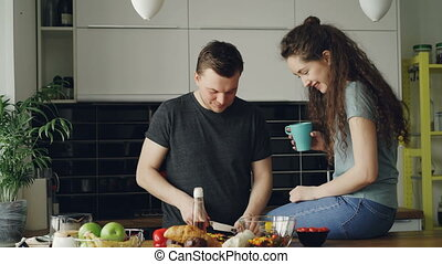 Happy young couple cooking ant talking in the kitchen at home. Attractive man feeding his girlfriend while cutting vegetables for breakfast in the morning
