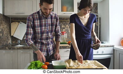 Happy young couple cooking in modern kitchen at home