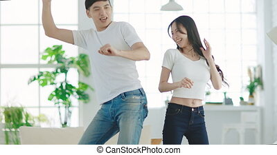 Happy young couple  dancing in living room at home