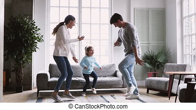 Happy young couple dancing with child daughter in living room