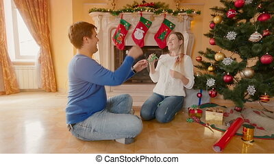 Happy young couple decorating Christmas tree and throwing tinsel at each other