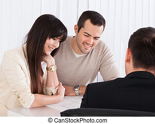 Happy Young Couple Discussing With Consultant