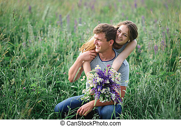 young couple embracing on summer meadow
